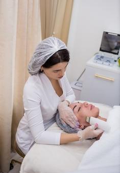 Eine kosmetikerin in weißer uniform macht eine ultraschallreinigung des gesichts der kundin