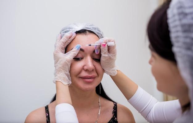 Eine kosmetikerin in weißer uniform macht eine verjüngungsspritze
