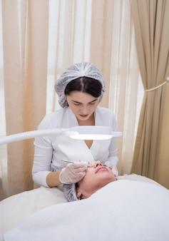 Eine kosmetikerin in weißer uniform und mütze macht eine mechanische reinigung für eine kundin auf der couch