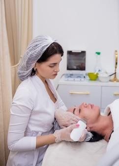 Eine kosmetikerin in weißer uniform und mütze macht eine ultraschallreinigung für eine kundin auf der couch