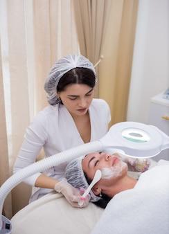 Eine kosmetikerin in weißer uniform und mütze macht eine verjüngende gesichtsmaske für eine kundin