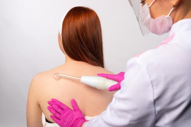 Eine kosmetikerin trägt darsonval auf und reibt es sanft über den gesamten rücken. gesundheits- und körperpflegekonzept. foto auf weißer wand.
