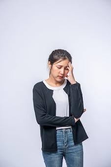 Eine kranke frau mit kopfschmerzen und legte ihre hand auf den kopf