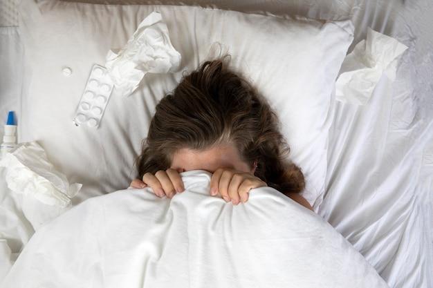 Eine kranke junge frau im bett, die mit dem kopf unter der decke liegt und neben ihr ein stapel taschentücher liegt