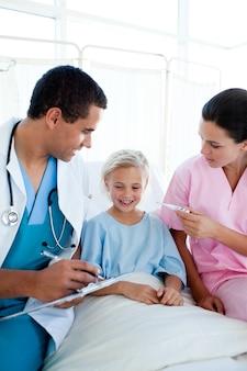 Eine krankenschwester, die die temperatur ihres patienten in einem krankenhaus nimmt