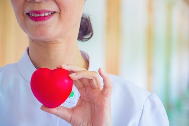 Eine krankenschwester, die rotes herzspielzeug hält. das foto zeigt den grundsatz des interessierens und der guten gesundheit.