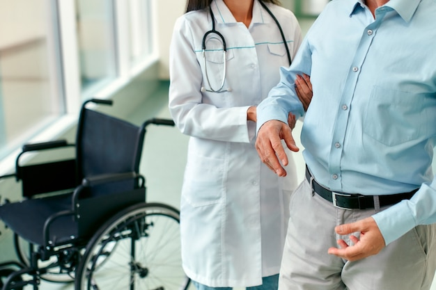Eine krankenschwester in medizinischer uniform hilft einem reifen behinderten patienten im rollstuhl, wieder laufen zu lernen. rehabilitation einer behinderten person in der klinik.
