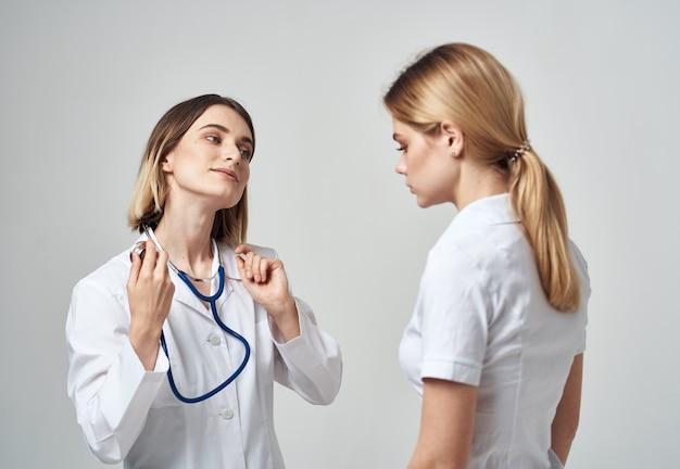 Eine krankenschwester mit einem stethoskop und einem patienten