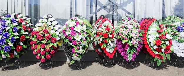 Eine kranzreihe zur beerdigung die trauerkränze sind aus plastikblumen
