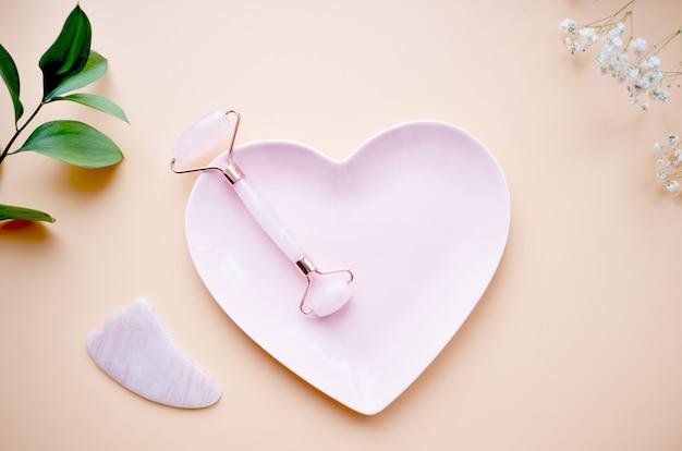 Eine kreative aufnahme eines modischen gua sha-massagewerkzeugs oder einer jadewalze auf einem rosa herzförmigen teller. entspannungs- und spa-konzept. flache lage, draufsicht. speicherplatz kopieren.