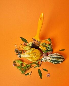 Eine kreative herbstkomposition mit einem pinsel aus grünen blättern mit blumen und dekorativen kürbissen auf einem orangefarbenen hintergrund