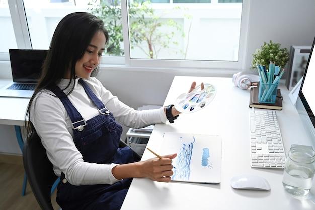 Eine künstlerin, die bild auf notizblock in ihrer werkstatt malt