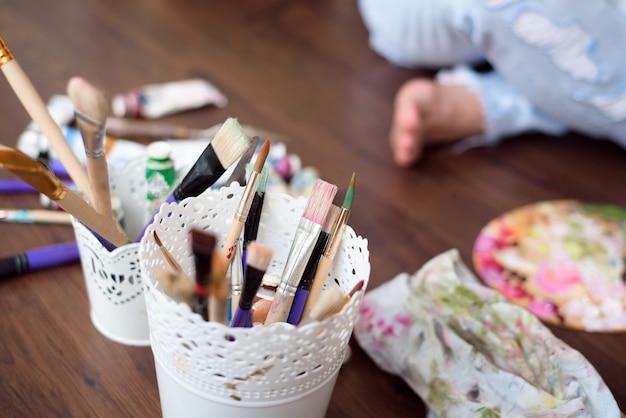 Eine künstlerin malt in ihrer werkstatt ein bild auf leinwand mit ölfarben