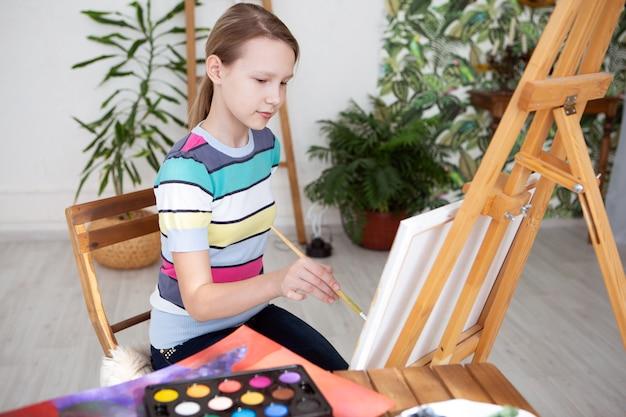 Eine künstlerin malt mit ölfarben ein bild auf leinwand