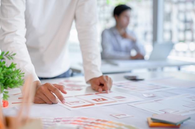 Eine kurze ansicht der kreativen ux ui-designer, die die programmierung und codierung mobiler anwendungen anhand des prototyp- und drahtgitter-layouts entwickeln.