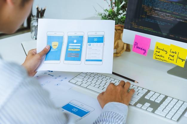 Eine kurze ansicht von ux-ui-front-end-designern, die ansprechende webinhalte oder mobile anwendungen aus prototyp- und drahtgitter-layouts programmieren und codieren.