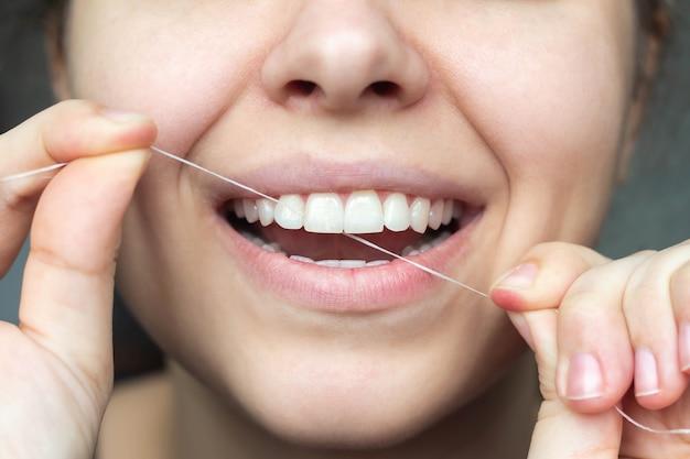 Eine kurze aufnahme einer jungen schönen frau, die ihre zähne mit zahnseide behandelt. nahansicht. zahnärztliches konzept