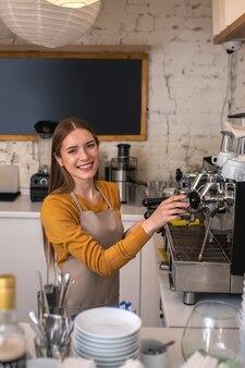 Eine lächelnde barista, die professionelle ausrüstung für ihre arbeit verwendet