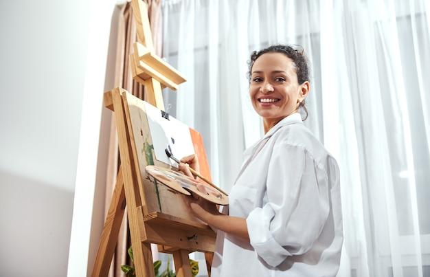 Eine lächelnde brünette malerin, die eine palette mit farbe und einem pinsel hält und vor einer staffelei steht.
