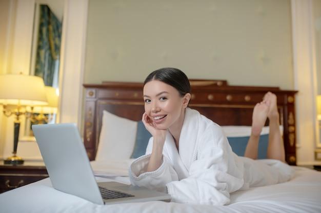 Eine lächelnde frau, die einen computer in ihrem schlafzimmer benutzt