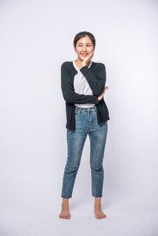 Eine lächelnde frau glücklich in einem schwarzen hemd, stehende jeans, glücklich lächelnd.