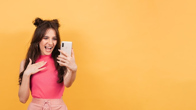 Eine lächelnde frau hält auf gelbem hintergrund ein smartphone, auf dem sie eine videonachricht aufzeichnet oder in einem videochat spricht. eine kopie des raums. platz für text