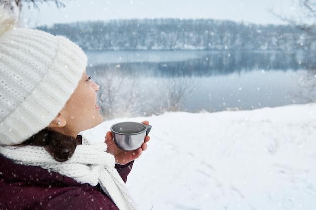 Eine lächelnde frau in der weißen strickmütze und im schal, die weg schauen und schönen schneebedeckten tag genießen