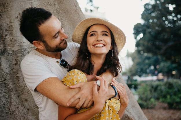 Eine lächelnde frau in einem hut und einem gelben kleid und ihr glücklicher freund mit bart umarmen sich unter einem alten valencianischen ficus macrophylla