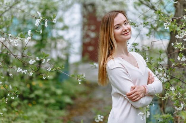 Eine lächelnde frau in einer weißen bluse steht in einer kirschblüte