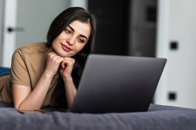 Eine lächelnde frau liegt vor ihrem laptop auf dem bett. arbeiten von zu hause aus im quarantäne-lockdown. soziale distanzierung selbstisolation