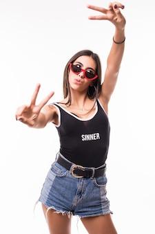 Eine lächelnde frau mit hosenträgern und roter sonnenbrille zeigt den sieg auf beiden händen