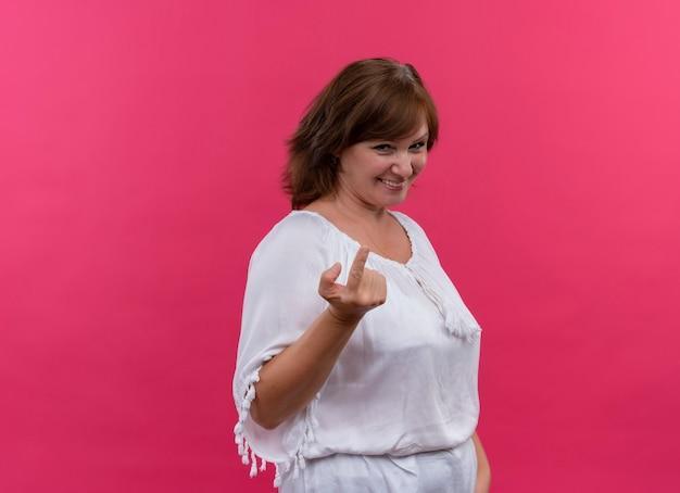 Eine lächelnde frau mittleren alters, die gestikuliert, kommt hierher und ruft sie an einer isolierten rosa wand an