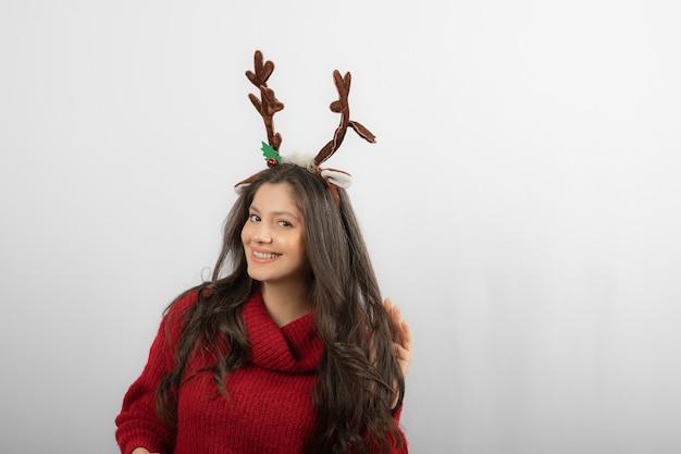 Eine lächelnde frau steht mit einem stirnband in form von weihnachtshörnern.