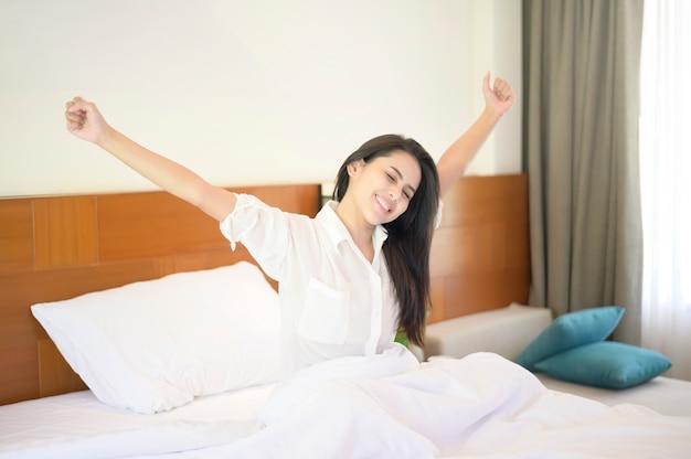 Eine lächelnde frau streckte ihre hände aus, nachdem sie morgens zu hause aufgewacht war.