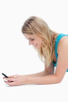 Eine lächelnde frau texting an ihrem handy