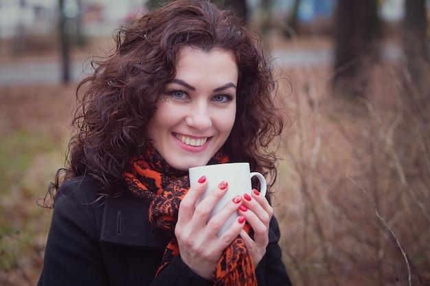 Eine lächelnde frau trinkt ihren heißen tee oder kaffee aus einer tasse
