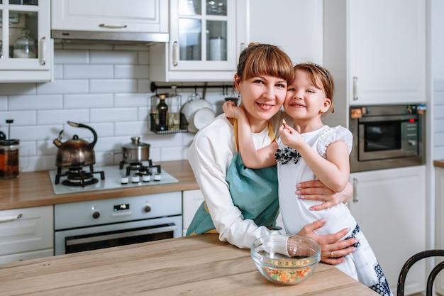 Eine lächelnde frau umarmt ihre mutter. leute in der küche