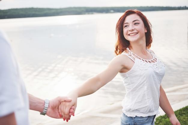 Eine lächelnde glückliche frau mit einem spielerischen ausdruck und einer hand mit ihrem ehemann.