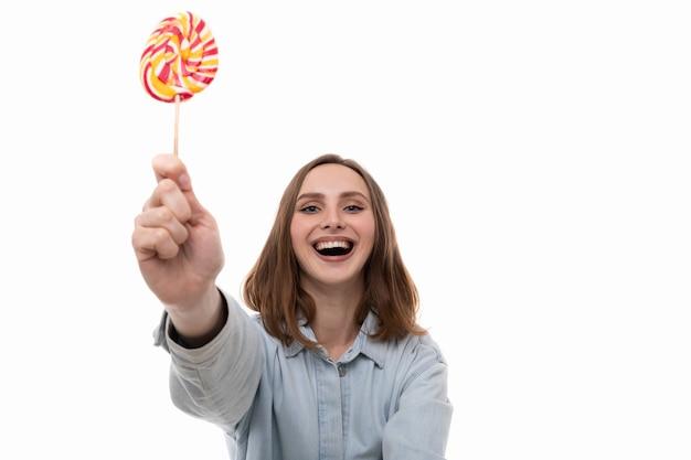 Eine lächelnde junge frau in einem jeanshemd wirft mit einem farbigen lutscher auf einem weißen hintergrund auf