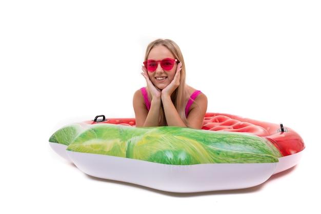 Eine lächelnde junge frau in einem rosa badeanzug liegt auf einem aufblasbaren schwimmkreis