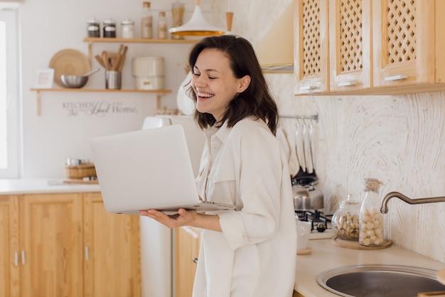 Eine lächelnde junge frau in einer küche genießt ein videogespräch und lernt sich auf einer website kennen. eine frau verbringt zeit in einem sozialen netzwerk
