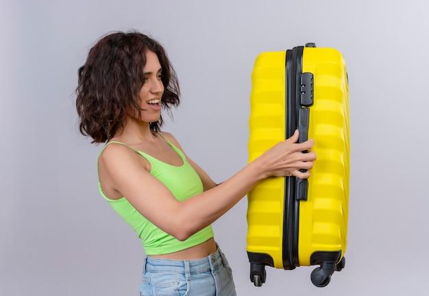 Eine lächelnde junge frau mit kurzen haaren in der grünen erntespitze, die gelben koffer auf weißem hintergrund hält