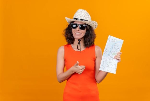 Eine lächelnde junge frau mit kurzen haaren in einem orangefarbenen hemd, das sonnenhut und sonnenbrille hält karte hält, die glücklich daumen hoch zeigt