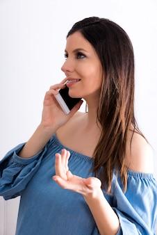 Eine lächelnde schwangere frau, die in einem wohnzimmer steht und auf ihrem telefon spricht