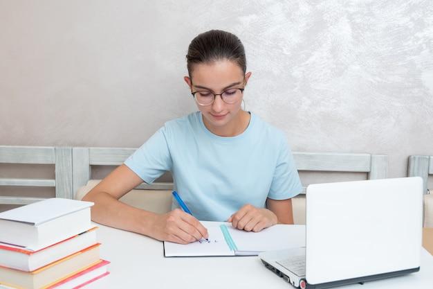 Eine lächelnde studentin, die mit einem laptop an einem tisch sitzt, schreibt eine aufgabe in ein notizbuch. studentin studiert zu hause. zurück zum schulkonzept. schulkonzept zu hause.