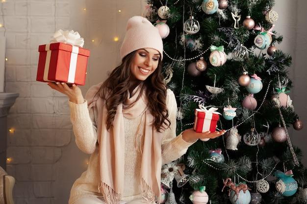 Eine lächelnde und glückliche junge frau in winterkleidung, die bequem auf dem boden neben dem weihnachtsbaum sitzt, öffnet ein geschenk