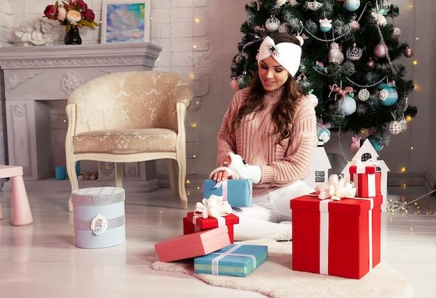 Eine lächelnde und glückliche junge frau in winterkleidung, die bequem auf dem boden neben dem weihnachtsbaum sitzt, öffnet ein neujahrsgeschenk. das mädchen genießt weihnachtsgeschenke, trifft das neue jahr und weihnachten.