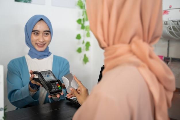 Eine lächelnde verschleierte geschäftsfrau hält ein edc-gerät, während ein kunde beim bezahlen eine kreditkarte hält.