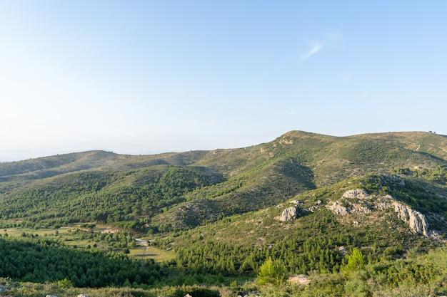 Eine landschaft aus bergen, umgeben von hügeln und einem pfad an einem sonnigen tag. emporda in katalonien, spanien
