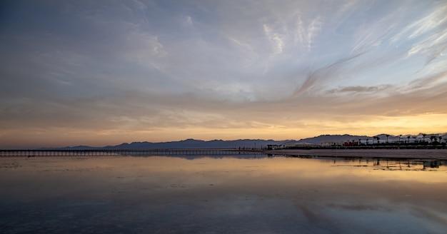 Eine landschaft des meeres mit einem langen pier und bergen am horizont.